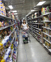 Woman in supermarket with shopping trolley