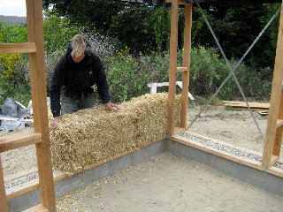 person placing a strawbale