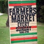 A sign with Hobsonville Point Farmers Market on it