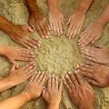 a circle of hands on a sandy beach